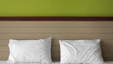 dual white pillow on bed at headboard and green wall in the room