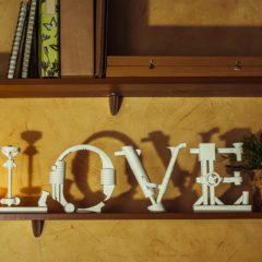 Diy love word made of paper standing on a bookshelf.